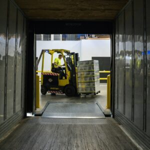 man loading cannabis into truck with forklift
